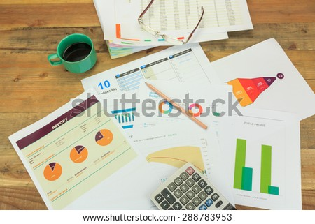 Business concept of a pencil, charts, eyeglasses, calculator, coffee cup - stock photo