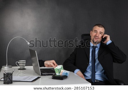 Business concept of internet scam. Thief hand stealing money of businessman - stock photo