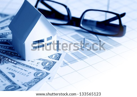 Business concept. Paper house near spectacles on one dollar bank notes on paper with chart - stock photo