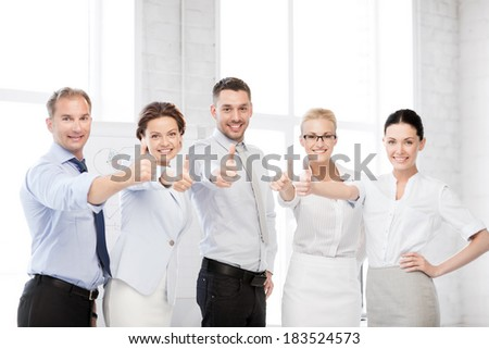 business concept - picture of happy business team showing thumbs up in office - stock photo