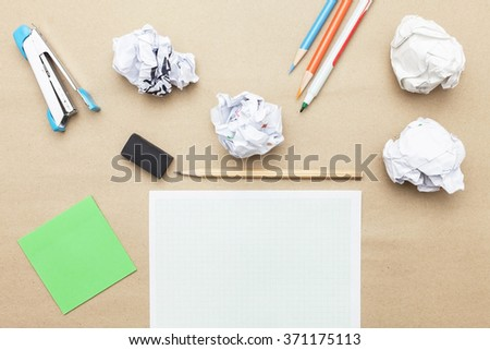 Business concept:red clock,white blank paper,crumpled paper and color pencil,pencil,pen on brown paper background - stock photo