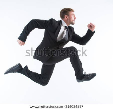 Business concept. Running young businessman excited, surprised and happy amazed isolated on white background. - stock photo