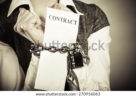 Business concept. Serious businesswoman with chained hands holding contract - stock photo