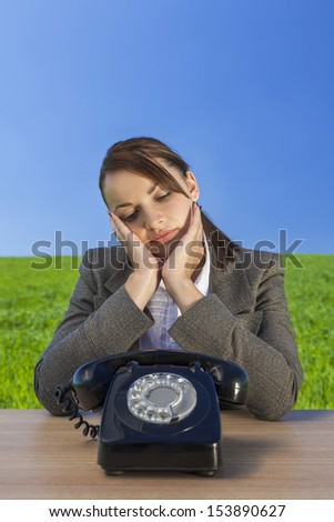 Business concept shot of a beautiful young woman businesswoman sitting at a desk waiting for old vintage telephone to call in  green field with a bright blue sky.  - stock photo