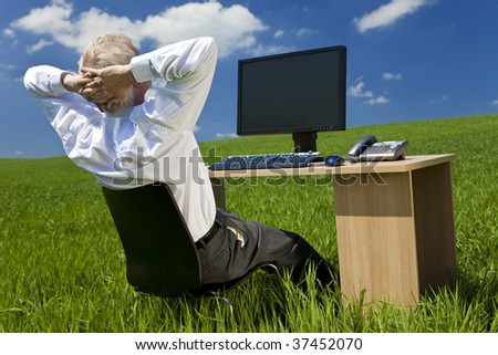 Business concept shot showing an older male executive relaxing at his desk with a computer in a green field with a blue sky complete with fluffy white clouds. Shot on location not in a studio. - stock photo