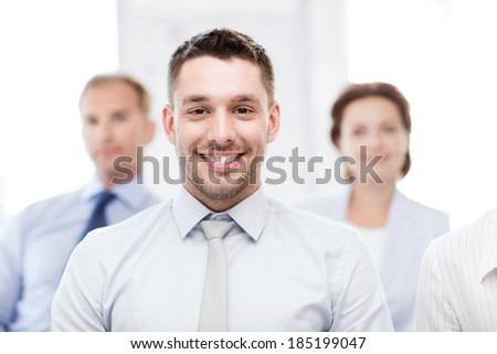 business concept - smiling handsome businessman with team in office - stock photo