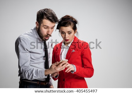 Business concept. The two young colleagues holding mobile phone on gray background - stock photo