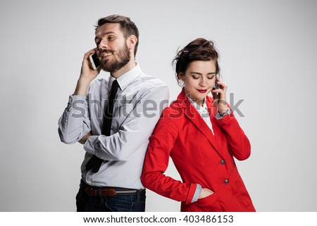 Business concept. The two young colleagues holding mobile phones on gray background - stock photo