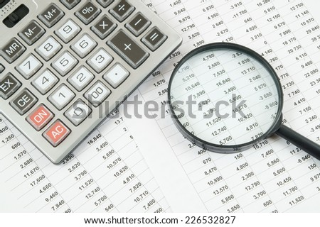 Business concept with calculator and magnifying glass on documents  - stock photo