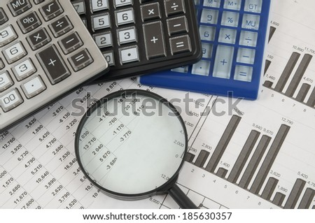 Business concept with three calculators and magnifying glass on documents  - stock photo