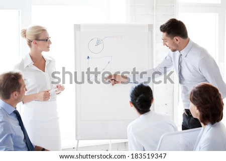 business concept - young businessman pointing at graph on flip board in office - stock photo