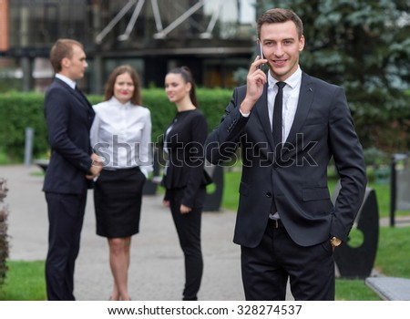 Business confidence. Portrait of motivated businessman. Successful leader is making a mobile phone call in business suit. Outdoors business concept. His business partners and colleagues on background - stock photo