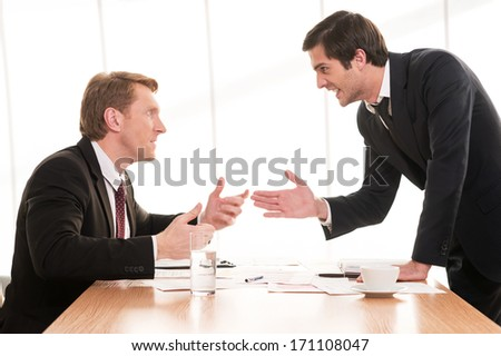 Business conflict. Two young men in formalwear arguing and gesturing while sitting at the table - stock photo
