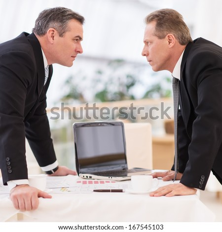 Business confrontation. Two mature men in formalwear conflicting while standing face to face - stock photo