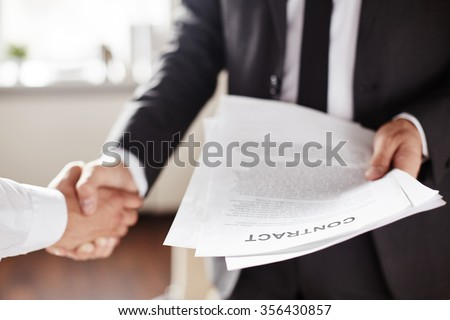 Business contract held by businessman during handshake with partner - stock photo