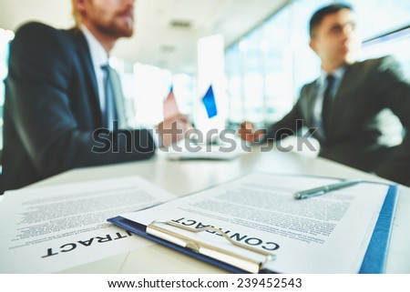 Business contracts on the desk with two male colleagues sitting on background - stock photo