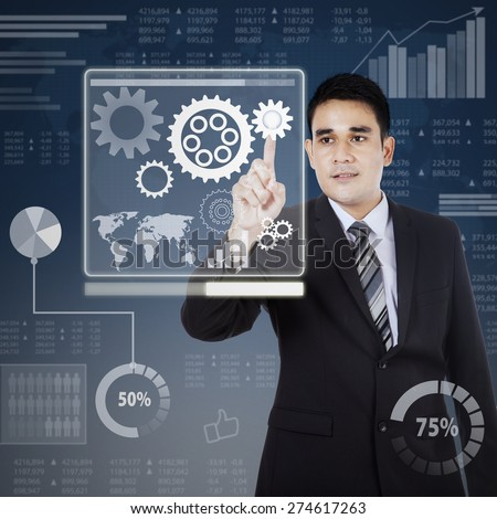 Business control concept. Young businessman touching gear to control business - stock photo