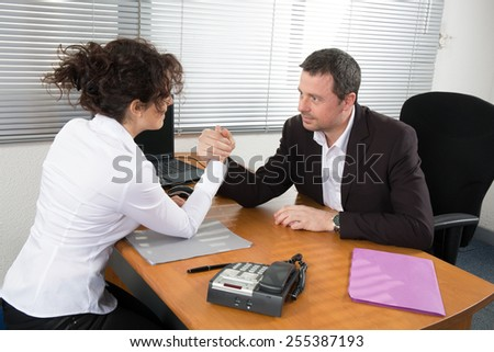 Business couple arm wrestling at the office - stock photo