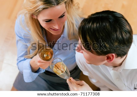 Business Couple - man and woman - at home with champagne sitting on the wooden floor clinking glasses - stock photo