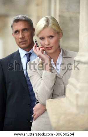 Business couple outside with a cellphone - stock photo