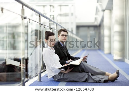 Business couple portrait - young man and woman working together on the floor of modern office corrdor - stock photo