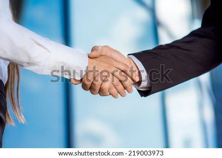 business couple shaking hands outdoors on contempopary background - stock photo