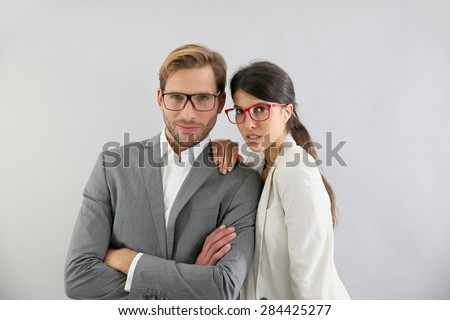 Business couple standing on grey background, isolated - stock photo