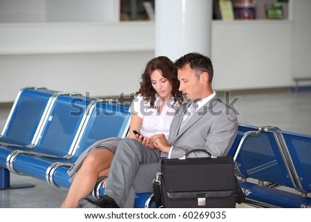 Business couple waiting at airport lounge - stock photo
