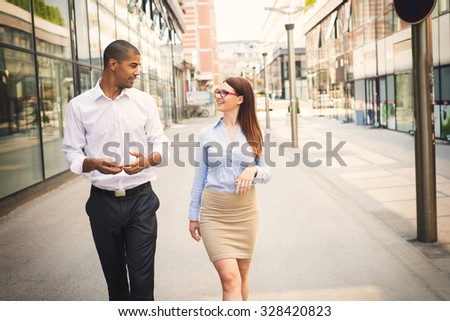 Business couple walking trough passage, looking each other and smiling. - stock photo