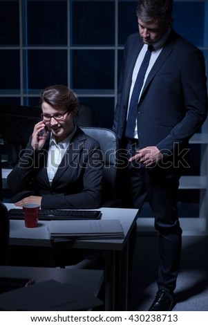 Business couple working at office at night, woman sitting beside desk, talking on cellphone - stock photo