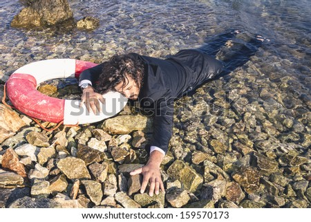 Business Crash. Man out of conscious at the beach washed by the sea.   - stock photo