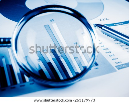 Business Data Analyzing, with magnifying glass and other on the desk. - stock photo