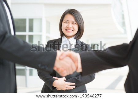 Business deal, Asian businessmen handshaking. Focus on assistant or secretary. Modern  office building architecture background. - stock photo