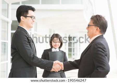 Business deal, Asian businessmen handshaking. Senior CEO hand shake with young executive. Modern  office building architecture background. - stock photo