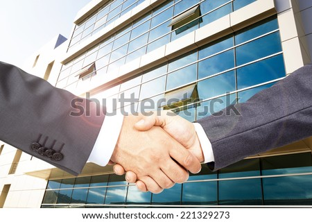 Business deal with business building backgraund - stock photo