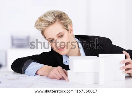 Business designer aligning white blocks as she sits at her desk assessing the best perspective for a product or advertisement - stock photo