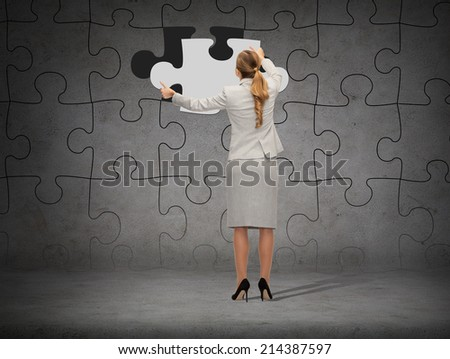 business, development and people concept - businesswoman in suit setting piece of puzzle to the wall background - stock photo