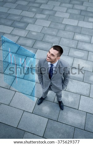 business, development, finances and people concept - young smiling businessman with forex chart on virtual screen outdoors from top - stock photo