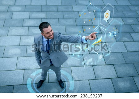 business, development, technology and people and concept - young smiling businessman pointing finger to virtual screens with graphs outdoors from top - stock photo