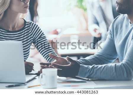 Business discussion. Close-up of two young business people discussing something while sitting at the office desk together while their colleagues sitting in the background - stock photo