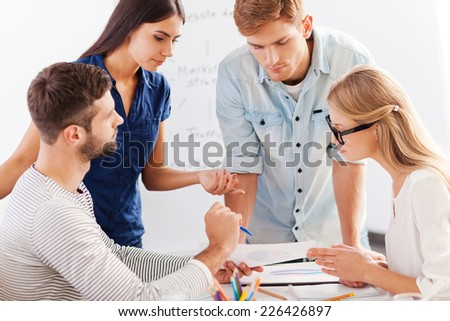 Business discussion. Four cheerful business people in smart casual wear discussing something while leaning at the table - stock photo