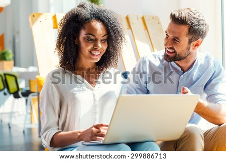 Business discussion. Smiling young African woman working on laptop while man sitting near her and gesturing - stock photo