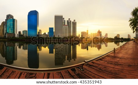 Business district cityscape from a park with sunrise time from Benchakitti  park, Bangkok Thailand - stock photo