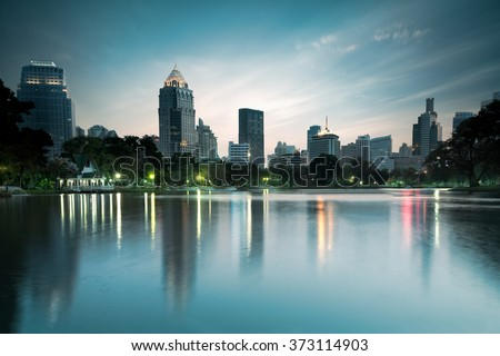 Business district cityscape from a park with twilight time from lumpini park, Bangkok Thailand - stock photo