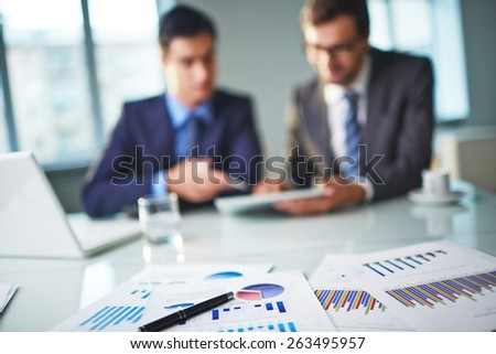Business documents at workplace and two businessmen networking on background - stock photo