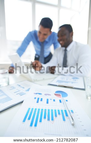 Business documents at workplace with two businessmen networking on background - stock photo