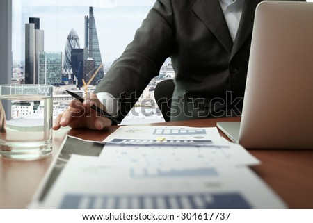 business documents on office table with smart phone and digital tablet and graph business diagram and man working in the background with london city view - stock photo