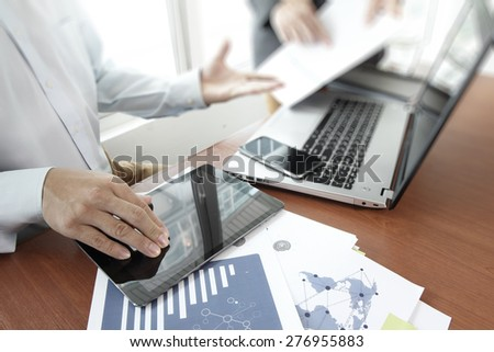 business documents on office table with smart phone and digital tablet and laptop computer and two colleagues discussing data in the background - stock photo