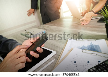 business documents on office table with smart phone and laptop computer and graph business  and three colleagues discussing data in the background                                - stock photo