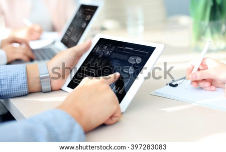 business documents on office table with smart phone and laptop computer and graph business with social network diagram and three colleagues discussing data in the background - stock photo